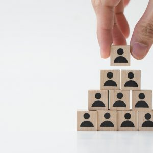Businessman stacking wooden team blocks