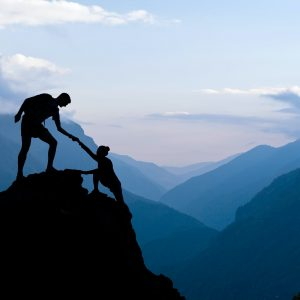 Teamwork couple climbing helping hand